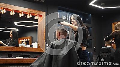 Atractiva barbería cortando el pelo de un hombre con tijeras y peine Cortadora de pelo que trabaja sirviendo al cliente Hombre el almacen de video
