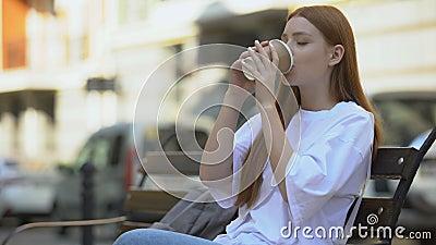 Atractiva chica disfrutando del sabor y aroma del café dulce caliente en vidrio de papel almacen de metraje de vídeo