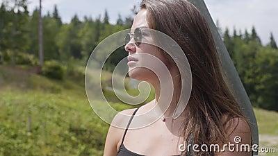 Atractiva joven con gafas mirando lejos mientras se sienta en el coche explorando la naturaleza salvaje. Chica de moda almacen de metraje de vídeo