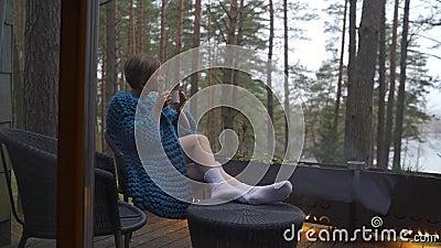 Atractiva muchacha en pijama sentada en un balcón con una taza de té o café, disfruta de la naturaleza almacen de video