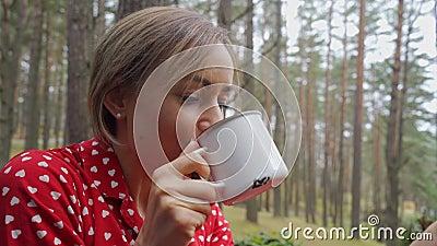 Atractiva muchacha en pijama sentada en un balcón con una taza de té o café, disfruta de la naturaleza metrajes