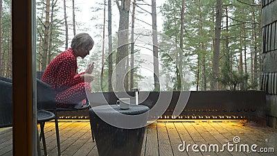 Atractiva muchacha en pijama sentada en un balcón con una taza de té o café, disfruta de la naturaleza almacen de metraje de vídeo