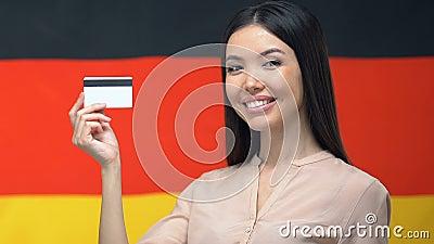 Atractiva mujer mostrando tarjeta de crédito en fondos de bandera alemana, fondos financieros metrajes