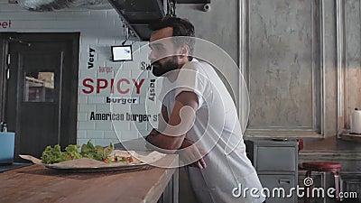 Atractivo joven con barba se para cerca del bar, esperando su hamburguesa. hombre elegante en un café. 4 kK. Vídeo de 4k. 30 fps almacen de video