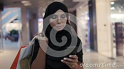 Atrakcyjna kobieta muzułmańska nosząca czarny chustę hijab chodząca w centrum handlowym i używająca smartfona Komunikacja zbiory wideo