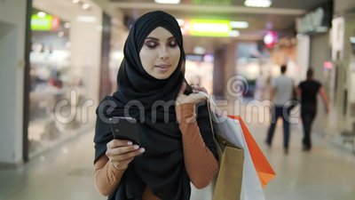 Atrakcyjna kobieta muzułmańska nosząca czarny chustę hijab chodząca w centrum handlowym i używająca smartfona Komunikacja zdjęcie wideo