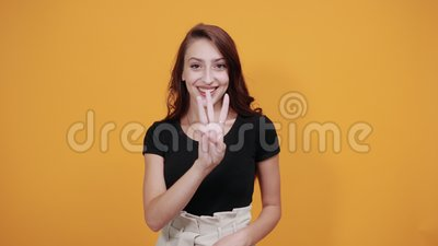 Atrakcyjna kobieta w czarnej koszuli, pokazująca trzy palce, uśmiechnięta, wygląda zabawnie zbiory