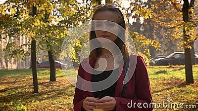Atrakcyjna młoda żeńska pozycja w parku, mienie żółtym liściu i patrzeć thoughfully na kamerze w piękny pogodnym, zdjęcie wideo