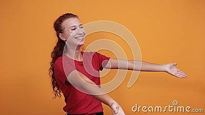 Atrakcyjna młoda dama w czerwonej koszuli wita, zaprosić kogoś ponad pomarańczową ścianą zbiory
