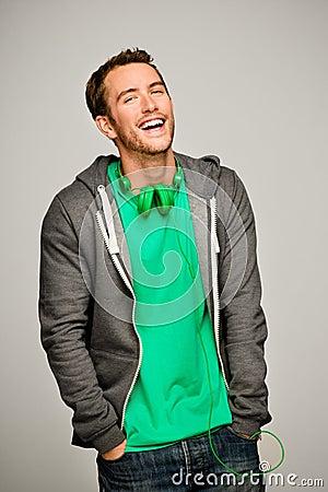 Atrakcyjny młody człowiek jest ubranym hoodie ono uśmiecha się
