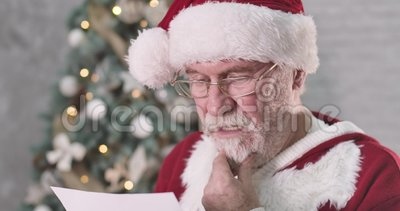 Att jultomten läste upp ett brev och missnöjde ansiktet Högre man med vitt skägg som funderar på gåva till stock video