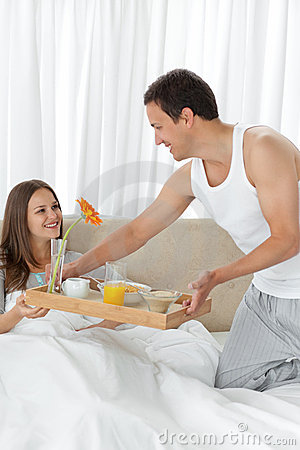 Attentive man bringing the breakfast to his wife