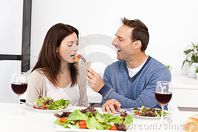 Attentive man giving a tomato to his girlfriend