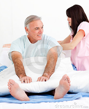 Attentive nurse fixing her patient s bed