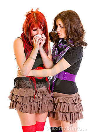Attentive young girl calming her sad girlfriend