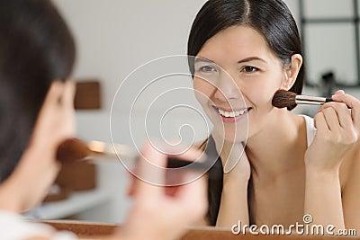 Attractiv happy woman applying makeup