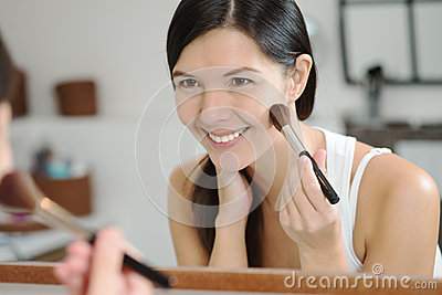 Attractiv happy woman applying makeup