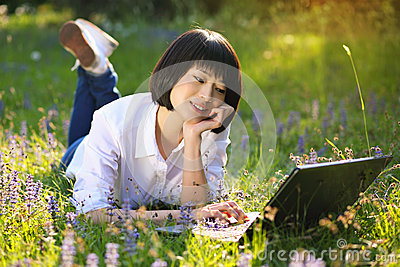 Attractive asian girl using laptop among flowers Stock Photo