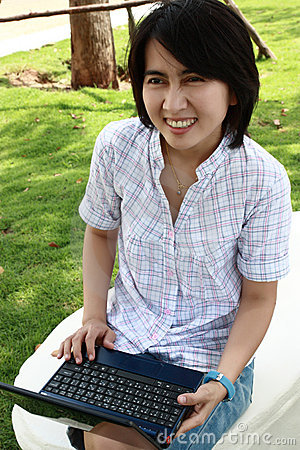 Attractive Asian woman is outdoors with laptop