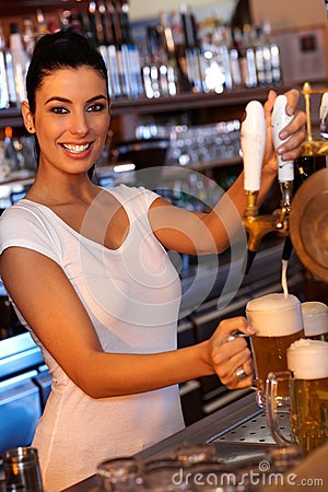 Attractive bartender tapping beer in bar