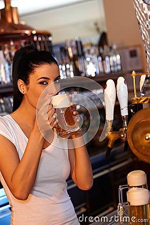 Attractive bartender tasting freshly draught beer
