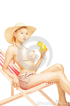Attractive blond female with hat sitting on a sun lounger and dr