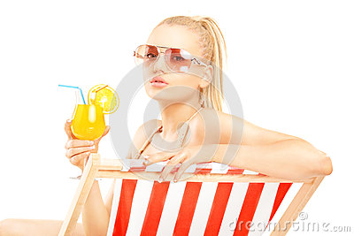 Attractive blond female sitting on a sun lounger and drinking a
