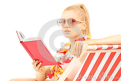 Attractive blond female sitting on a sun lounger and reading a b
