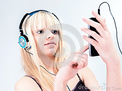 Attractive blond girl listening to music on her smartphone