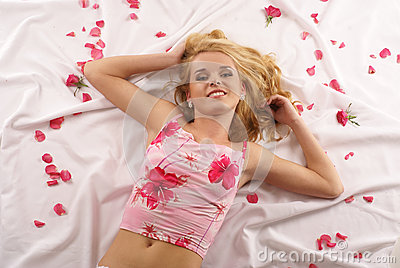 Attractive blond on a white blanket with petals