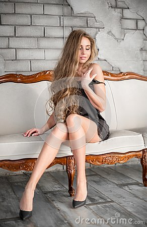 Free Attractive Blond Woman In Black Dress Sitting On The Couch Royalty Free Stock Images - 117425409