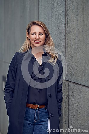 Free Attractive Blond Woman Leaning Against An Urban Concrete Wall Stock Images - 113727734