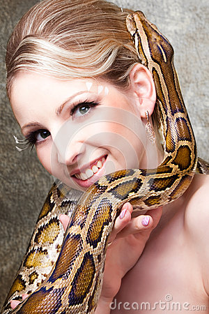 Attractive blond woman with python on grey