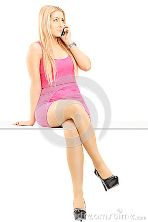 Attractive blond woman talking on a phone and sitting on a table