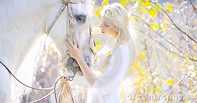 Attractive blonde cutie touching royal horse
