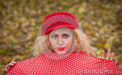 Attractive blonde girl with red cap looking over red umbrella outdoor shoot. Attractive young woman in a autumn shoot.
