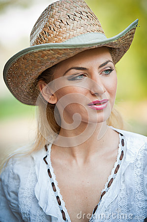 Attractive blonde girl with straw hat and white blouse