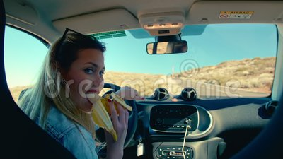 Attractive blonde woman eating a banana as a symbol of men, sitting on the driver`s seat of a car and holding the. Steering wheel. Concept car driver woman stock video footage