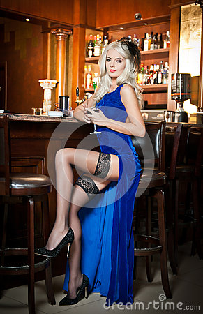 Free Attractive Blonde Woman In Elegant Blue Long Dress Sitting On Bar Stool Holding A Glass In Her Hand. Gorgeous Blonde Model Royalty Free Stock Image - 35607786
