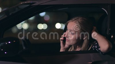 Attractive blonde woman talking on phone in car stock video