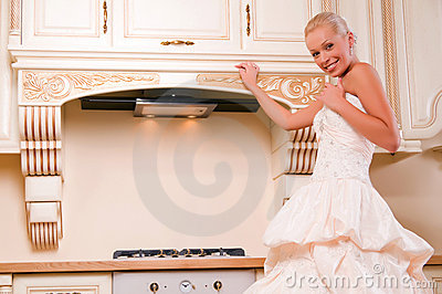 Attractive bride stands in the kitchen