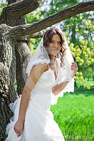 Attractive Bride stands about trees
