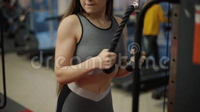Attractive brunette with slender physique and cute face doing exercise on simulator. One person 20s 30s with sports. Clothing train in gym club indoors interior stock video footage