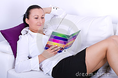 Attractive brunette studying book on white couch