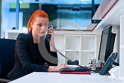 Attractive business woman in office cubicle on the phone