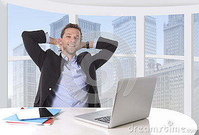 Attractive businessman happy at work smiling relaxed at computer business district office Stock Photo