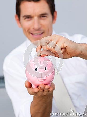 Attractive businessman saving money in a piggybank