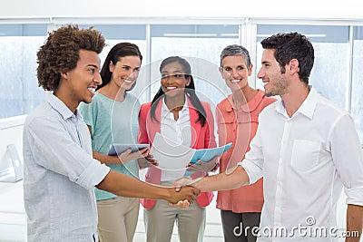 Attractive businessmen shaking hands at work