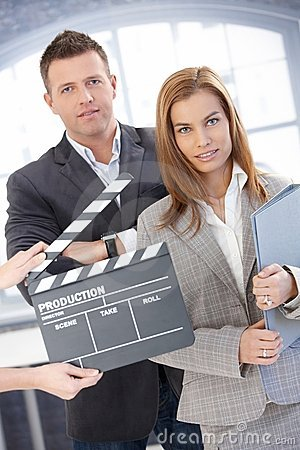 Attractive businesspeople with clapper board