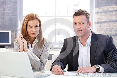 Attractive businesspeople working on laptop